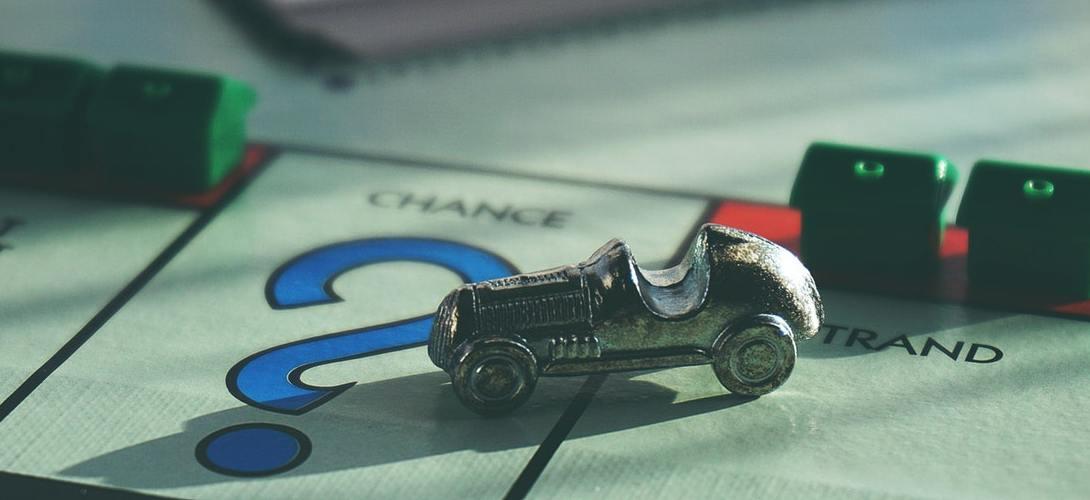 Monopoly Spielfeld mit einer Autospielfigur auf einem Feld mit einem Fragezeichen und der Aufschrift Chance
