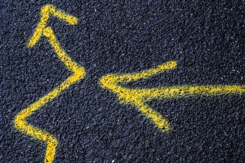 gelbe Zick-Zack-Pfeile auf Asphalt gemalt